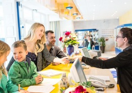 Family buying tickets at reception